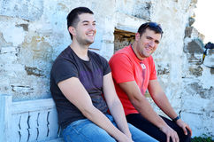 Portrait of two beautiful young men sitting on a bench and laughing Stock Images