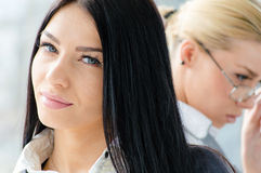 Portrait of two beautiful young women brunette & blond co-workers near office window at daytime stock photography
