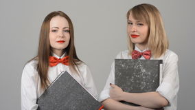 Portrait of two beautiful young women. With butterflies on their neck smiling, emotions. Leading, entertainer with folders in the studio stock footage
