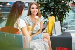 Pretty Girls in Shopping Mall. Portrait of two beautiful young women chatting in shopping mall, sitting on couch in hall and eating ice-cream Royalty Free Stock Image