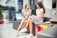 Two Girls in Shopping Mall. Portrait of two beautiful young women chatting in shopping mall, sitting on couch in hall relaxing with coffee Royalty Free Stock Image