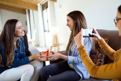 Two beautiful young women exchanging a gift while their friend takes a photo at home. Portrait of two beautiful young women exchanging a gift while their friend Stock Image