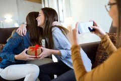 Two beautiful young women exchanging a gift while their friend takes a photo at home. Portrait of two beautiful young women exchanging a gift while their friend Royalty Free Stock Images