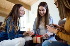Two beautiful young women exchanging a gift while their friend takes a photo at home. Portrait of two beautiful young women exchanging a gift while their friend Stock Photo