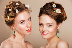 Portrait of two beautiful young women with perfect makeup and hairstyle wearing jewelry Stock Photos