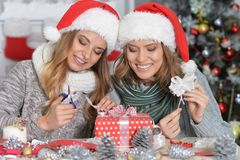 Girls preparing for Christmas. Portrait of two beautiful young women in santa hats preparing for Christmas Royalty Free Stock Image