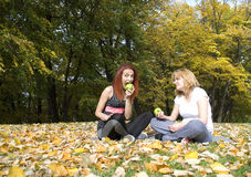 Portrait of two beautiful young women sitting together, smiling, resting from exercize and eating green apple Royalty Free Stock Photography