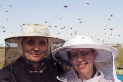 Portrait of two beekeeper surrounded by bees. Horizontal portrait of two beekeepers, father and daughter, surrounded by swarmming bees Stock Photography