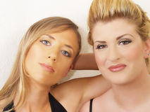 Portrait of two blond women against white wall. Two blond caucasian women portrait close together Stock Image