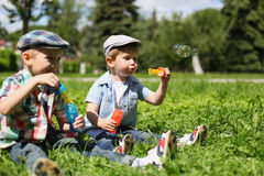 Portrait of two boys children sitting on the grass blowing soap Royalty Free Stock Photography