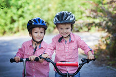 Portrait of two boys in the park, riding bike and scooter Stock Image
