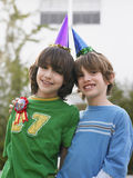 Portrait Of Two Boys In Party Hats Outdoors Royalty Free Stock Photography