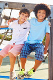 Portrait Of Two Boys On Playground Climbing Frame Stock Image