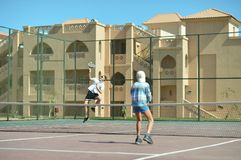 Two boys playing tennis. Portrait of two boys playing tennis at court stock photos
