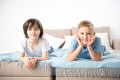 Little happy companions lying on bed. Portrait of two boys resting on bedding. They are looking at camera with pleasure Royalty Free Stock Photography