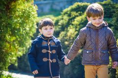 Portrait of two boys, siblings, brothers and best friends smilin. G. Friends hugging. Happy kids wearing warm closes in spring green garden Stock Photos