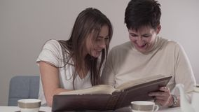 Portrait of two brunette Caucasian women of different ages watching photo album. Young-looking mother and her beautiful