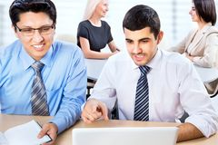 Portrait of two business men with colleagues. Behind them Royalty Free Stock Photos