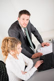 Portrait of two business people working together in office with computer Royalty Free Stock Images