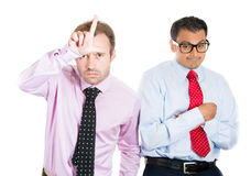 A portrait of two businessmen: a bully standing upfront showing a loser sign and a nerd, shy guy wearing glasses standing behind h Royalty Free Stock Photos