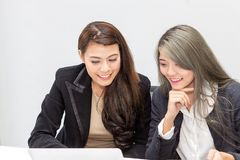 Portrait of two businesswoman using laptop in office. Female in stock photo