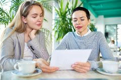 Two Business Women Reading Contract. Portrait of two businesswomen holding contract sitting at table in modern office and reading terms Royalty Free Stock Photo