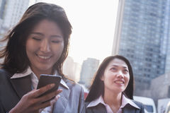 Portrait of two businesswomen, one looking at phone, outdoors Beijing Stock Image