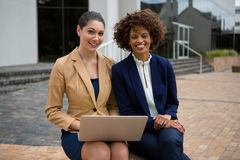 Portrait of two businesswomen using laptop stock images