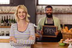 Portrait of two casual waiters holding a board written open Royalty Free Stock Image