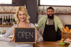 Portrait of two casual waiters holding a board written open Stock Image