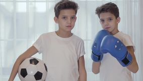 Portrait of two Caucasian twin brothers with black hair posing with ball and boxing gloves. Young schoolboys going in