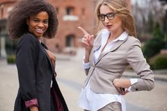 Portrait of two charming african and caucasian businesswomen smiling and posing for camera. stock photo