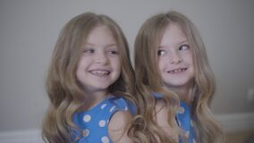 Portrait of two cheerful Caucasian twin sisters sitting back to back, talking and laughing. Happy children in similar