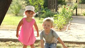 Portrait of two cheerful children in a summer Park. Two funny small kids in the Park, they are playing and having fun. Portrait of two cheerful emotional stock video
