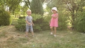 Portrait of two cheerful children in a Sunny Park. Two funny small kids in the Park, they are playing and having fun. Portrait of two cheerful emotional stock footage