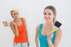 Portrait of two cheerful female friends holding paintbrushes Royalty Free Stock Images