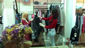 Two girls buy new clothes in a fashion store in a large shopping center. Portrait of two cheerful girls in a clothing store, they choose and try on coats and stock footage