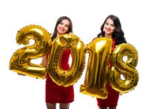 Portrait of two cheerful happy girls in red dresses posing with gold colored number balloons isolated over white background, New 2. Portrait of two cheerful Stock Photos