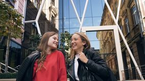Portrait of two cheerful stylish Caucasian girlfriends walking along street near modern building while laughing and stock video