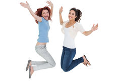 Portrait of two cheerful young female friends jumping Stock Photos