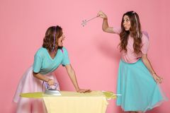 Portrait of a two cheerful young girls ironing clothes. On a pressboard while standing with an iron an a magical wand  over pink background Stock Image
