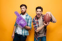 Portrait of a two cheerful young men holding rugby ball stock photo