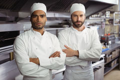 Portrait of two chefs standing together with arms crossed in commercial kitchen. At restaurant stock image