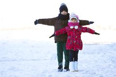 Portrait of two children boy and girl playing outdoors in winter. Snowy day stock image