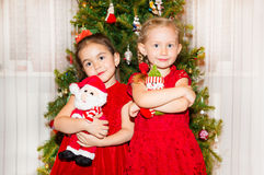 Portrait of two children girls around a Christmas tree decorated. Kid on holiday new year Stock Images