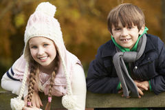 Portrait Of Two Children Leaning Over Wooden Fence Stock Photo
