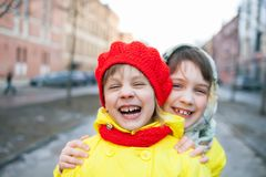 Two little sisters in   winter city. Portrait of two children outdoors in early spring royalty free stock image