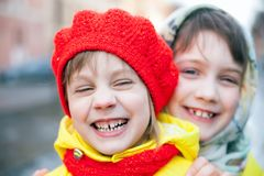 Portrait of two children outdoors in early spring. Two little sisters in winter city stock image