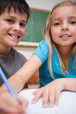 Portrait of two children writing Royalty Free Stock Photos