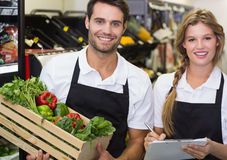 Portrait of two colleagues holding a box with fresh vegetables and writing on notepad. At supermarket stock photos